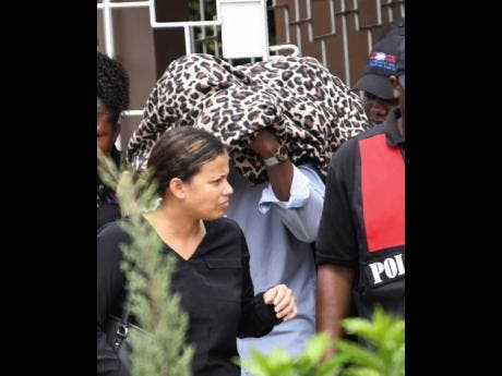 Attorney Carolyn Chuck (left) and members of the Major Organised Crime and Anti-Corruption Agency escort Ruel Reid and his family to a bus during a raid on his St Andrew home yesterday morning.