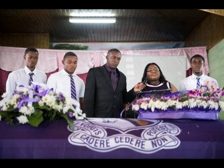 Kingston College representatives (from left): Shamari Jennings, Oshane Peart, coach Richard Smith, vice principal Juliet Wilson and track team captain Shanthamoi Brown pay tribute the late Twayne Crooks.