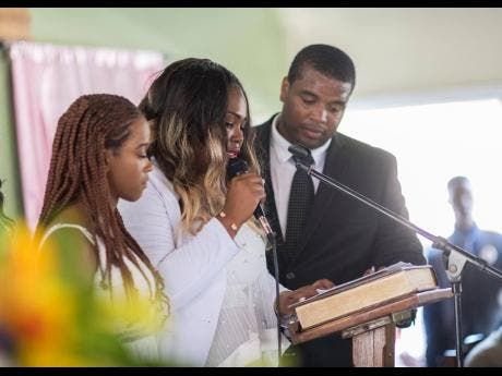 Andre Plummer (right) and Kadine Octable (left) consoles Tameka Pettigrew, who is overcome with grief as she reads a tribute from the cousins to the late Twayne Crooks.