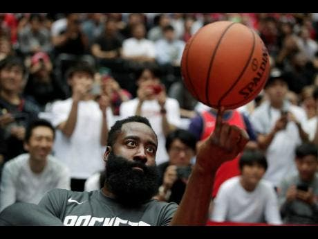 Houston Rockets' James Harden spins the ball during warm-ups for the team's NBA preseason basketball game against the Toronto Raptors  October. 10, 2019, in Saitama, near Tokyo.