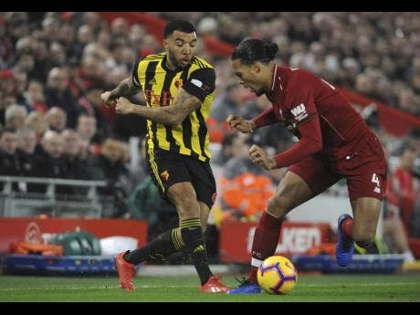 Watford's Troy Deeney (left) duels for the ball with Liverpool's Virgil van Dijk during their English Premier League game at Anfield Stadium in Liverpool, England on Wednesday, February 27, 2019.
