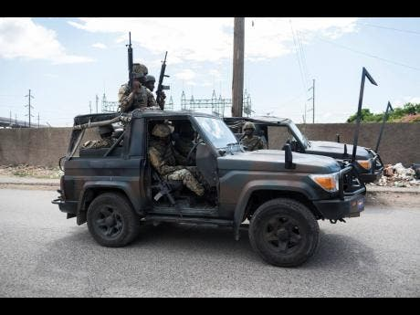 Members of the Jamaica Defence Force patrol the area yesterday following the shooting.