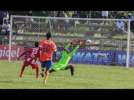 Lennon's goalkeeper Jovaun Grant (right) makes a point blank save to deny BB Coke's Kaymani Case (left) during their ISSA/WATA daCosta Cup second-round first-leg game at the Juici Patties Park yesterday.