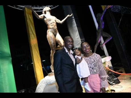 Veronica Campbell-Brown, her husband Omar Brown and daughter Avianna pose in front of the newly unveiled statue at Statue Park at the National Stadium on Sunday.