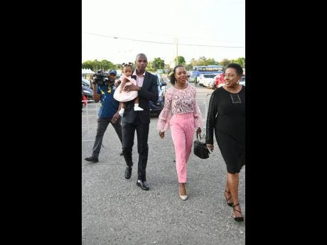Veronican Campbell-Brown (right) walks to Statue Park for the unveiling of her statue with husband Omar and daughter Avianna on October 20, 2019.