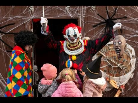 Mario Leicht (centre) and his wife wear costumes as horror clowns at their house, decorated for Halloween, in Walschleben near Erfurt, Germany, last Thursday. The whole house facade and the front garden are decorated with dolls, spiders, and skulls and inside with mini-ghosts, vampires, skeletons, zombies and almost 50 spiders. He has decorated the house for Halloween every year since 2011.
