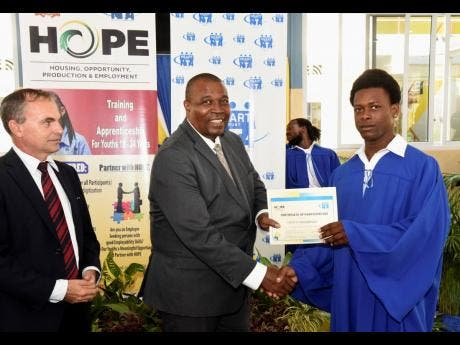 Genus Thompson (right) collecting his certificate from Assistant Commissioner of Police Devon Watkiss. HOPE Programme National Coordinator Martin Rickman looks on.