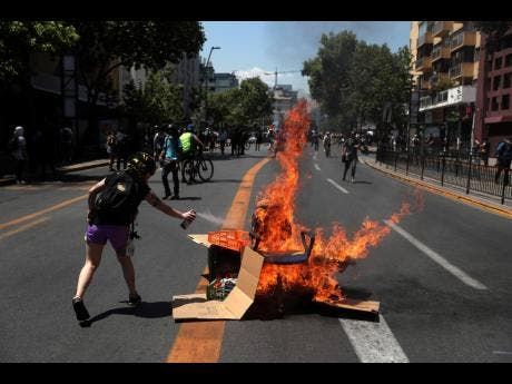 An anti-government demonstrator fuels a burning barricade with aerosol spray during a protest, in Santiago, Chile, yesterday. Chile's president is sending a bill to Congress that would raise the minimum salary, one of a series of measures to try to contain nearly three weeks of anti-government protests.