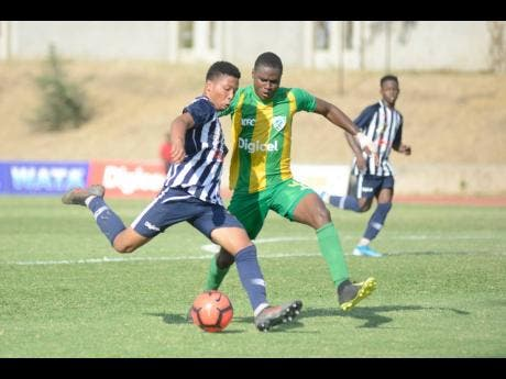 Jamaica College's Oquassa Chong (left) shoots while under pressure from Excelsior High School defender Roshawn Amas during their ISSA/Digicel Manning Cup quarter-final game at Stadium East yesterday.