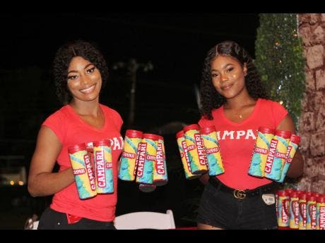 Campari ladies Sashoy Brown (left) and Vanessa McDonald were on site making sure fete-goers had their mugs ready for the fun at Xodus Carnival's Enchanted cooler launch.