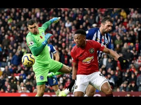 Brighton goalkeeper Mathew Ryan (left) makes a save in front of Manchester United's Anthony Martial during their teams' English Premier League match at the Old Trafford Stadium in Manchester, England, yesterday.