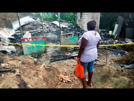 Judette Thorpe looking at her burnt-out home.