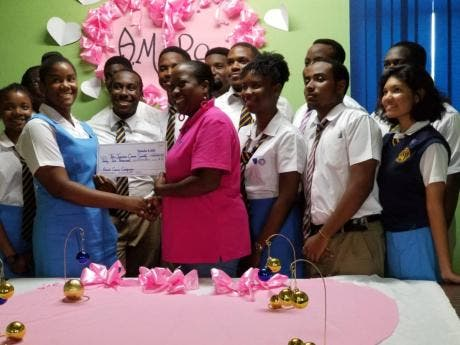 The Aspiring Medical Professionals Society of Ardenne High School presents a cheque for $42,000 to Shullian Brown (centre), public relations officer of the Jamaica Cancer Society.