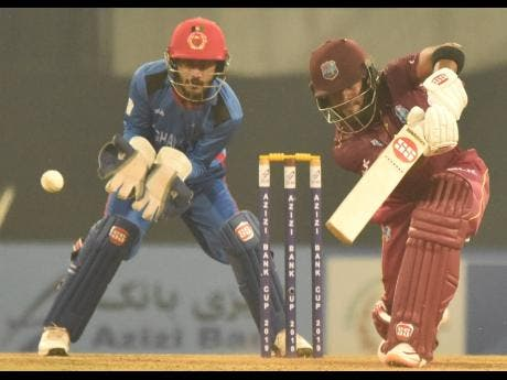 Windies batsman Shai Hope (right) drives for four on his way to an unbeaten century as Afghanistan wicketkeeper Ikram Alikhil looks on during their third and final one-day international match at the Atal Bihari Vajpayee International Stadium in Lucknow, India, yesterday. Hope won the Man-of-the-Match award.
