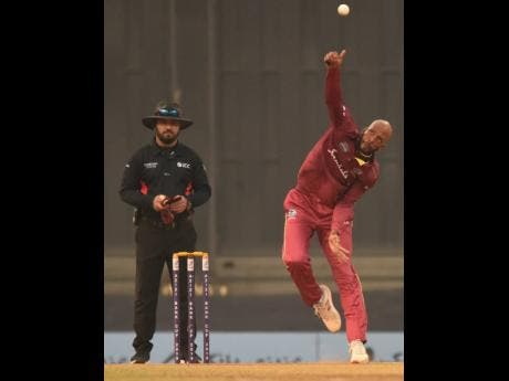 Windies bowler Roston Chase (right) bowls a delivery as umpire Ahmed Shah Durrani looks on during the third and final one-day international match against Afghanistan at the Atal Bihari Vajpayee International Stadium in Lucknow, India, yesterday. Chase was named Man of the Series.