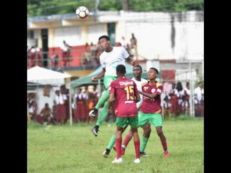 Frome Technical High School's Clifton Suban clears the ball from ahead of Green Island High School defenders during their ISSA/WATA daCosta Cup match at the Green Island field on Tuesday, October 9, 2018.