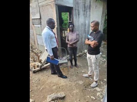 Contributed Photos Constable Anderson (left) and Sargeant Christopher Ward of the Annotto Bay Police Station in St Mary speak to Karen Samuels about rebuilding her home.