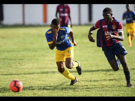 Papine High School's Alex Hutchinson (left) gets in a foot race with St Andrew Technical's Nicholas Bennett for possession of the ball during their ISSA/Digicel Manning Cup encounter at the Edward Seaga Complex on Friday, September 20, 2019.