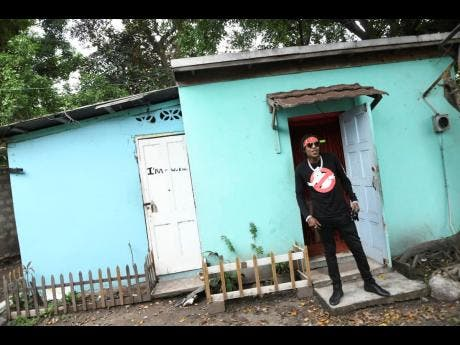 Dancehall artiste, Savage standing infront his 'likkle blue house'