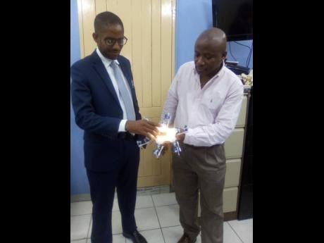 Principal of Spanish Town High Dr Ventley Brown (left) looks on as Martin Baker shows off the hexopad.