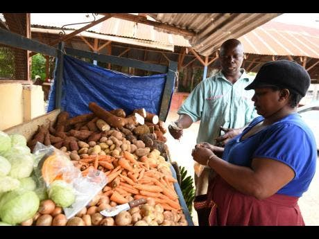 Yvette Nation (right) sells some produce to customer Pie Levy.
