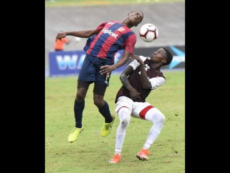 St Andrew Technical High School's Romario Campbell (left) tries to win a header ahead of Wolmer's Boys School's Ty McKetty during their ISSA/Digicel Manning Cup semi-final match at the National Stadium in St Andrew, yesterday.