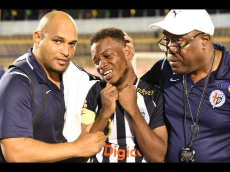 Jamaica College's Omar Thompson (centre) is overcome with emotion after the win against their rivals Kingston College, and is consoled by team manager Ian Forbes (right) and his assistant Darren Virtue.