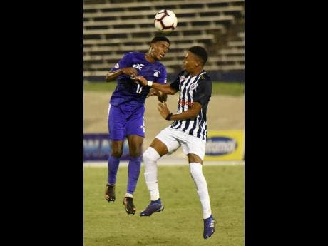 Kingston College's Sajar Blair (left) beats Jamaica College's Tyrese Small to a header during their ISSA/Digicel Manning Cup semi-final clash at the National Stadium in St Andrew last night.