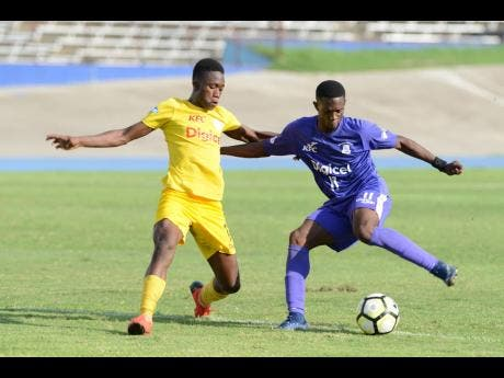 Renaldo Robinson of Kingston College tries to get away from  Charlie Smith High School's  Kareem Griffiths in their ISSA/Digicel Manning Cup encounter at the National Stadium on Thursday, October 31, 2019.