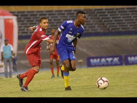 Clarendon College's Jamari Morrision (right) eludes Cornwall College defender Kamali Powell in the semi-final of the ISSA Champions Cup on November 16, 2019 at the National Stadium.