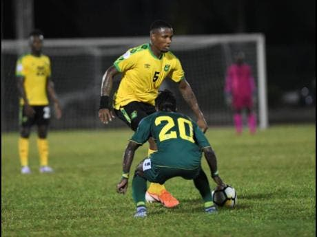 Jamaica's Alvas Powell tries to move past Guyana's Trayon Bobb in their Nations League encounter last Monday.