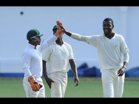 Jamaica's wicketkeeper Carlton Baugh (left) celebrates with Jamie Merchant (right) after he takes a wicket against Guyana in the regional four-day tournament in 2014.