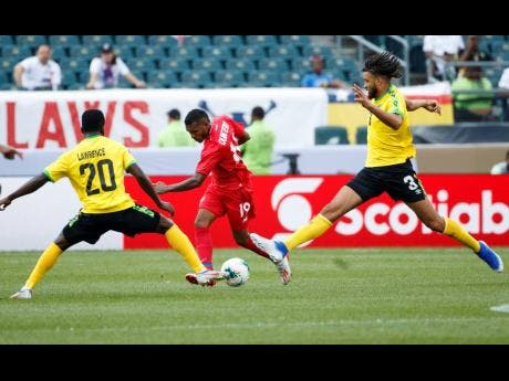 Panama's Alberto Quintero (centre) kicks the ball past Jamaica's Kemar Lawrence (left) and Michael Hector during the first half of a  Concacaf Gold Cup match on June 30, 2019.
