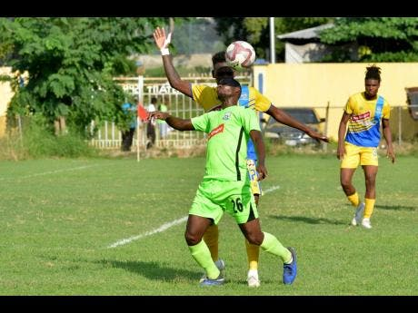 Harbour View's Damion Thomas engages Molynes United's Romario Campbell (front) in an aerial battle for possession in their Red Stripe Premier League game at the Constant Spring field yesterday.