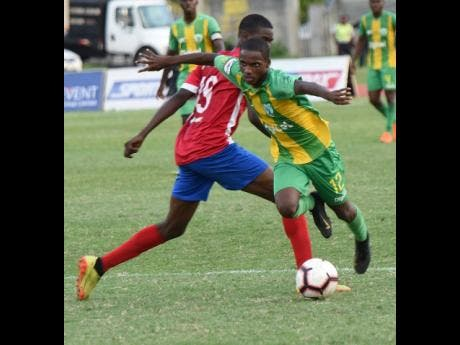 Ian Allen Photo Sheldon Butler (right) from Excelsior High evades a tackle from Rasheed Grant (left) from Camperdown High during their Walker Cup semi-final football match at the national Stadium East field on  November 21, 2019.