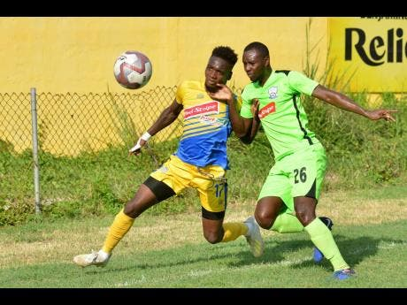 Harbour View's Damion Thomas (left) battles with Molynes United's Romario Campbell in their Red Stripe Premier League match at the Constant Spring football field on Wednesday.