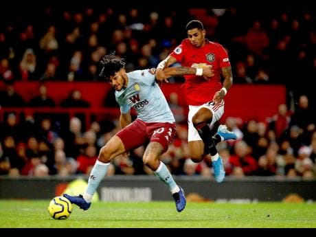 Aston Villa's Tyrone Mings (left) and Manchester United's Marcus Rashford battle for the ball during their teams' English Premier League football match at Old Trafford, Manchester, England, yesterday.
