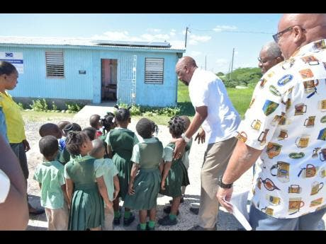 Member of Parliament for Clarendon South East Rudyard Spencer (third right) directs students to view the newly installed solar panels at the St Peter's Basic School.