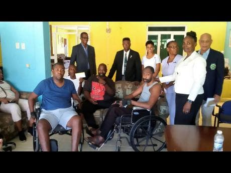 Members of the Association of Past Members of the Jamaica Constabulary Force Benevolent Society (Chapter One) with residents of the Convalescence Home.