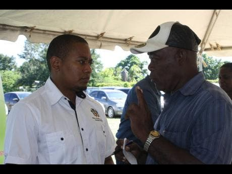 State Minister in the Ministry of Industry, Commerce, Agriculture and Fisheries, Floyd Green (left), in discussion with Cecil Lodge, a resident of Lionel Town, Clarendon, at a job fair hosted by the HEART/Trust NTA in collaboration with the Ministry of Industry, Commerce, Agriculture and Fisheries, the National Irrigation Commission (NIC) and the Rural Agricultural Development Authority, at Pawsey Park in the parish on November 29.