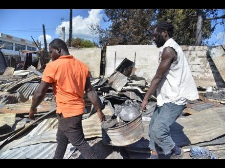 These men remove scrap metal after the blaze.