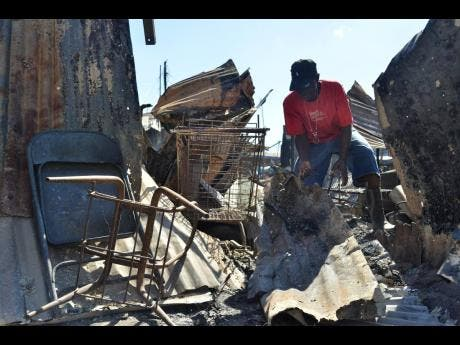 Glatston March searches through the rubble of what was once his shop. It was destroyed in the massive blaze that occurred on Sunday in a section of the May Pen Market.