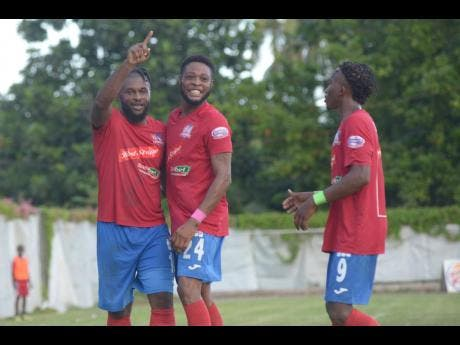 Dumbeholden's goalscorer Dean Andre Thomas (centre) celebrates with teammates Andre McFarlane (left)  and Demario Phillips (right) after finding the back of the net against UWI FC on October 27.