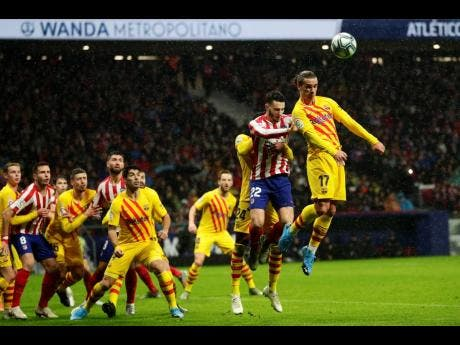 FC Barcelona's Antoine Griezmann (right) heads for the ball during a Spanish La Liga match between Atletico Madrid and FC Barcelona at Wanda Metropolitano stadium in Madrid, Spain, on Sunday, December 1, 2019.