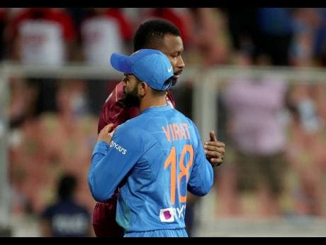 West Indies' captain Kieron Pollard (rear) hugs India's captain Virat Kohli after their win in the second T20 international cricket match yesterday.