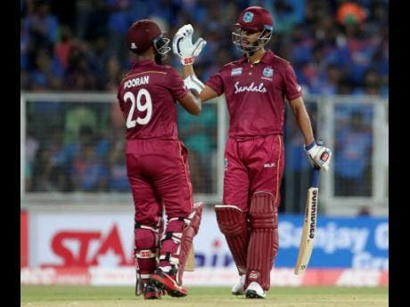 West Indies' Lendl Simmons (right) celebrates with batting partner Nicholas Pooran after their win in the second T20 international cricket match against India yesterday.