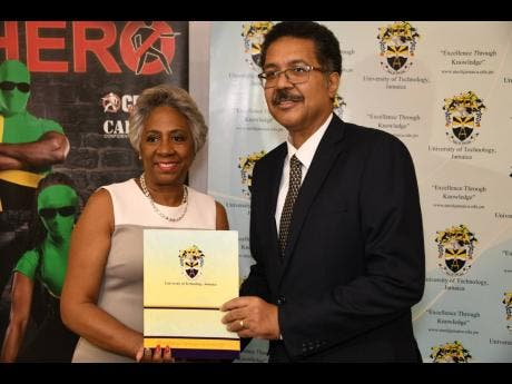 Professor Stephen Vasciannie, president of the University of Technology, hands over the module for the web-based platform to Sandra Glasgow, chairperson of the National Crime Prevention Fund at Crime Stop.
