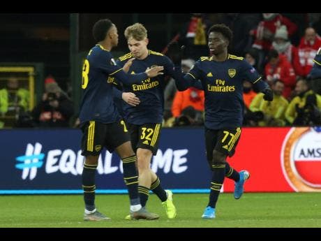 From left: Arsenal's Joe Willock Rowe, Emile Smith and, Bukayo Saka celebrate a goal during the Europa League group F match between Standard Liege and Arsenal at the Maurice Dufrasne stadium in Liege, Belgium, yesterday.