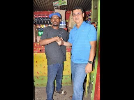 Rohan Elison (left) thanks Garth Young, operator of Young's Pharmacy in May Pen, Clarendon. Young was one of the sponsors who assited Elison with restocking hs shop.