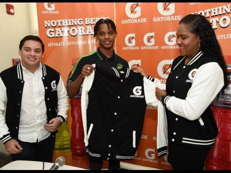 Peter-Lee Vassell (centre) displays a Gatorade jacket shortly after signing a two-year contract to become a brand ambassador for Gatorade Jamaica. Looking on are Michael Castillo (left), commercial director, and Cornelia Nathan, brand manager, both of Gatorade, Jamaica.